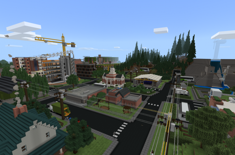 An aerial view of a city featuring a house, a building under construction, and a stand of evergreen trees in Minecraft: Education Edition
