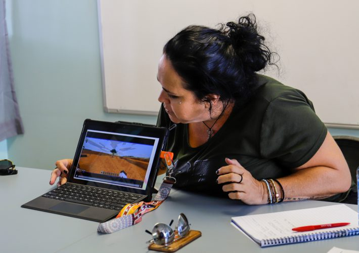 A woman sits behind a laptop displaying a tree in Minecraft: Education Edition.