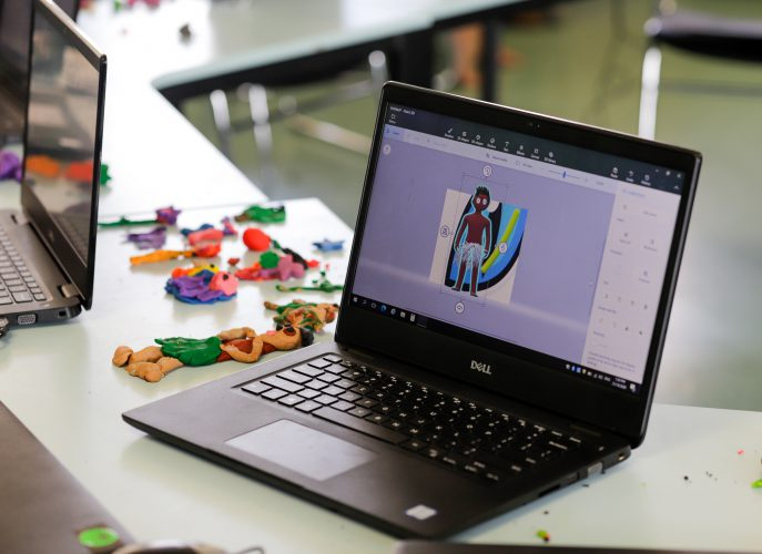 A student generates a 3D model of a character in Paint 3D on a laptop.