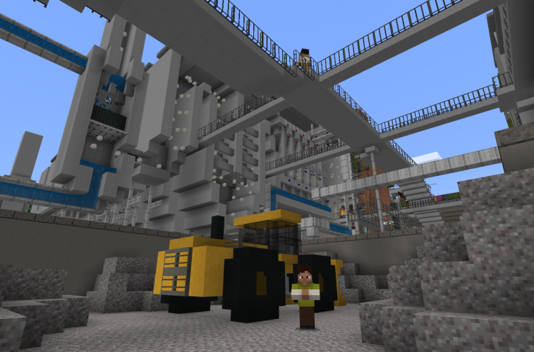A person stands next to a bulldozer in an industrial complex in Minecraft: Education Edition