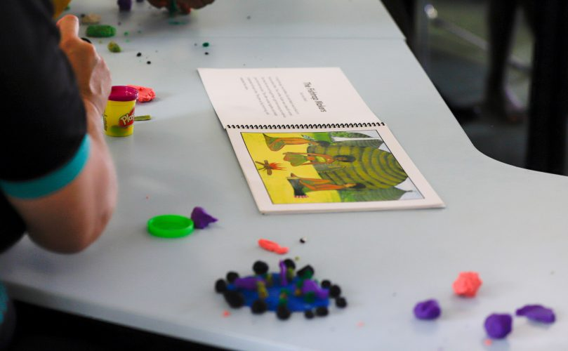 A student models a character from an indigenous storybook using modeling clay.