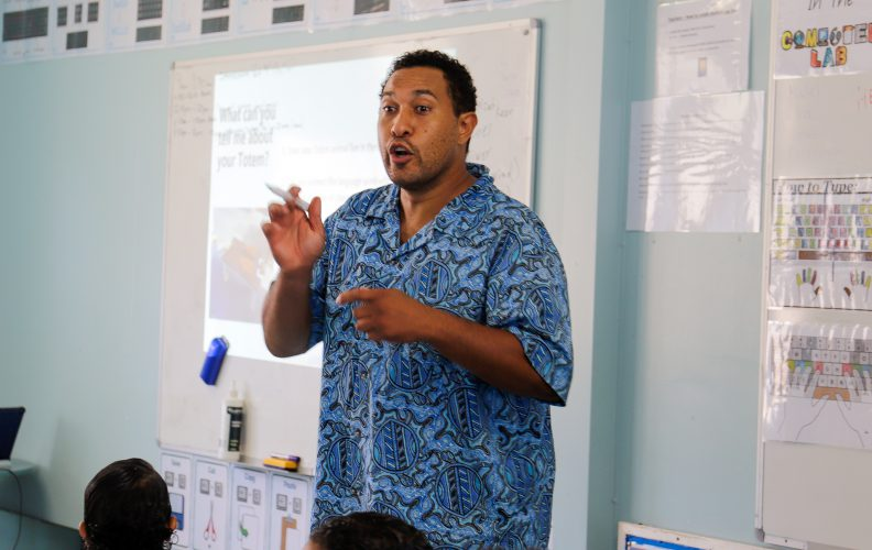 A man lectures at the front of a class.