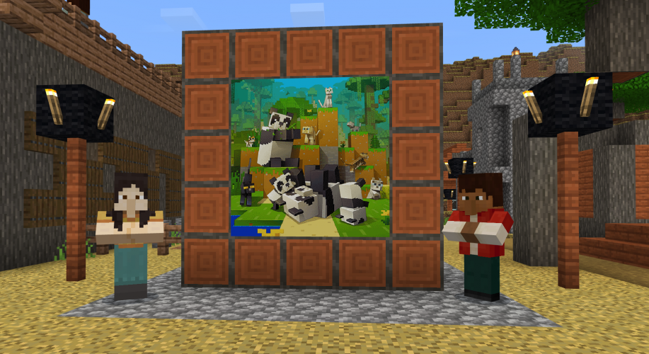 Two people stand in front of a mural featuring pandas and cats in Minecraft: Education Edition