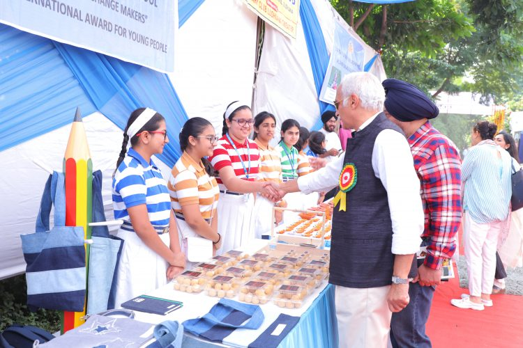 Two dignitaries shake hands with a group of girls standing behind a sales kiosk in a an open-air market.